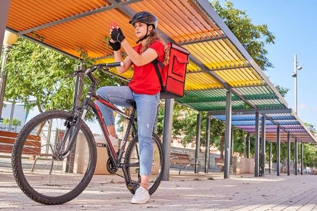 Kobieta dostarczająca rowerzystę sprawdza adres zamówienia na swoim smartfonie