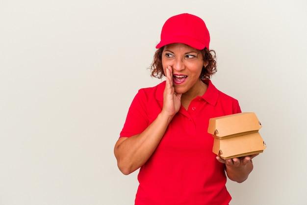 Kobieta dostarczająca w średnim wieku, biorąca hamburgery na białym tle, mówi tajne gorące wiadomości o hamowaniu i patrzy na bok