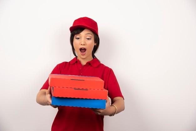 Kobieta dostawa pizzy pracownik stojący z trzema kartonami pizzy.
