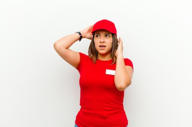 Kobieta dostawy czuje się zestresowana, zmartwiona, niespokojna lub przestraszona, z rękami na głowie, panikując w błędzie na tle bieli