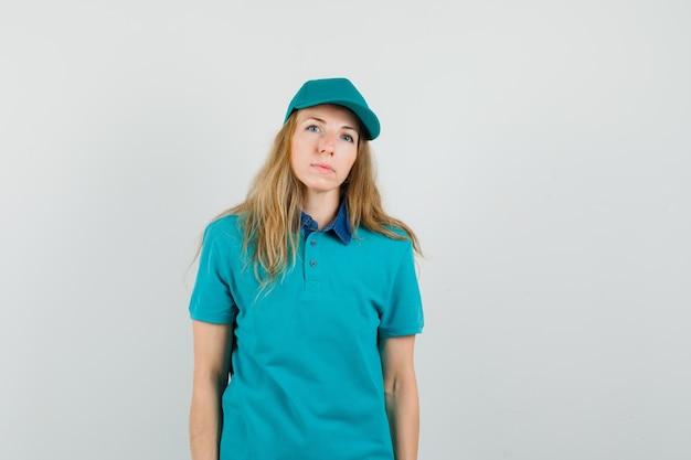 Kobieta dostawy patrząc na kamery w koszulce, czapce i rozsądnie wyglądającej
