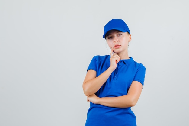 Kobieta dostawy patrząc w niebieską koszulkę i czapkę i patrząc zamyślony