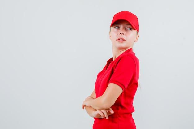 Kobieta dostawy patrząc wstecz ze skrzyżowanymi rękami w czerwonej koszulce i czapce i patrząc zaciekawiony. .