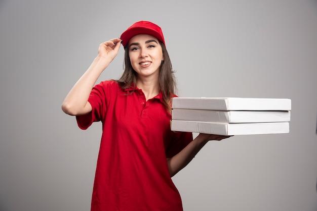 Kobieta dostawy pizze na szarej ścianie.