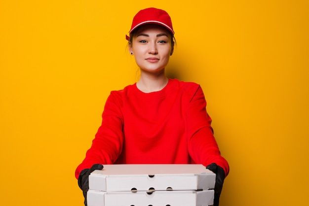 Kobieta dostawy pizzy posiadająca trzy pola na białym tle na żółtej ścianie