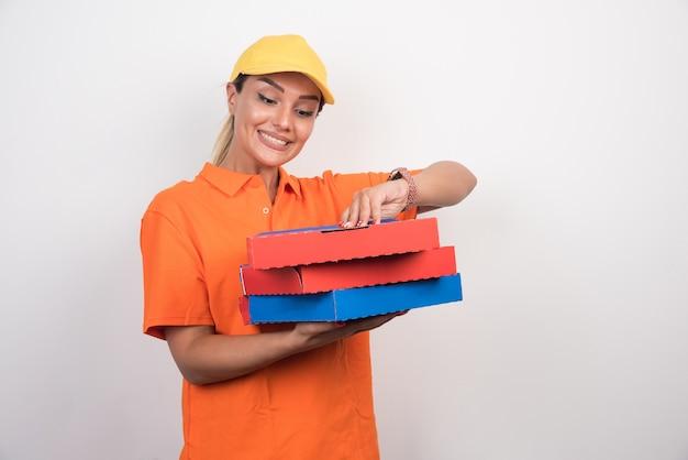 Kobieta dostawy pizzy próbuje otworzyć pudełko po pizzy z radosną buźką.