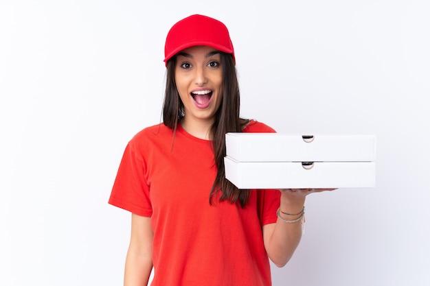 Kobieta dostawy pizzy trzyma pizzę na białej ścianie z zaskoczenia i zszokowany wyraz twarzy