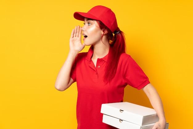 Kobieta dostawy pizzy trzyma pizzę na izolowanej ścianie krzyczy z szeroko otwartymi ustami z boku