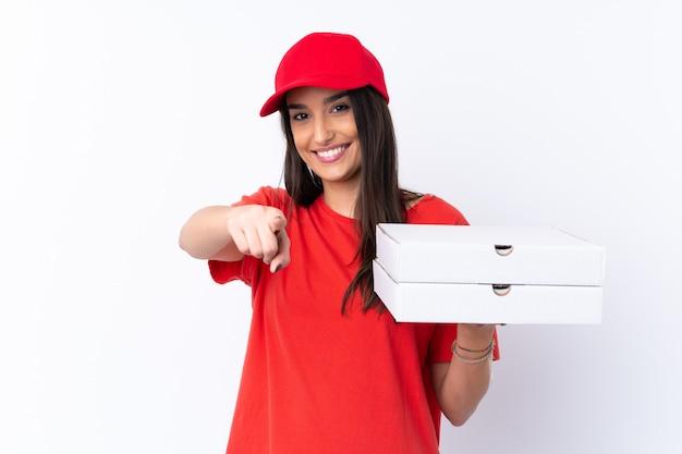 Kobieta dostawy pizzy trzyma pizzę na pojedyncze białe punkty ściany palcem na ciebie z pewną miną