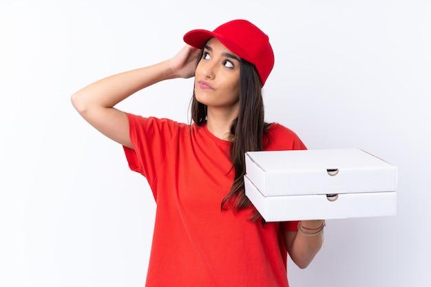Kobieta dostawy pizzy trzyma pizzę na pojedyncze białe ściany, mając wątpliwości i mylić wyraz twarzy