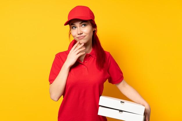 Kobieta dostawy pizzy trzyma pizzę nad izolowane ściany coś knuje