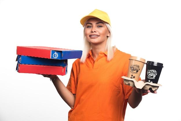 Kobieta dostawy pizzy trzymając pizzę i kawy na białym tle. wysokiej jakości zdjęcie