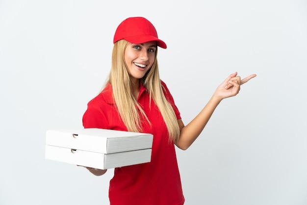 Kobieta dostawy pizzy trzymając pizzę na białym tle na białej ścianie, wskazując palcem na bok