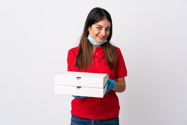 Kobieta dostawy pizzy trzymając pizzę na białym tle na białej ścianie z happy wypowiedzi
