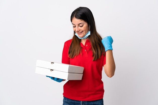Kobieta dostawy pizzy trzymając pizzę na białym tle świętuje zwycięstwo