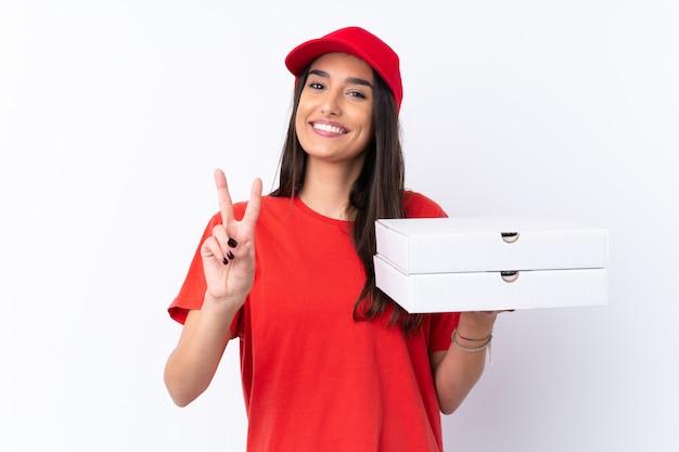 Kobieta dostawy pizzy, trzymając pizzę na pojedyncze białe ściany, uśmiechając się i pokazując znak zwycięstwa