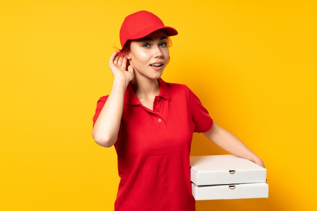 Kobieta dostawy pizzy trzymając pizzę na ścianie izolowane słuchanie czegoś, kładąc rękę na ucho