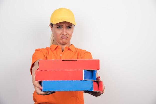 Kobieta dostawy pizzy trzymając pudełka po pizzy na białym tle.