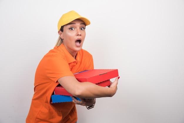 Kobieta dostawy pizzy trzymając pudełka po pizzy z zaskoczoną twarzą na białym tle.