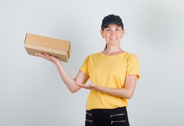 Kobieta dostawy pokazująca karton w t-shirt, spodnie, czapkę i zadowolony wygląd