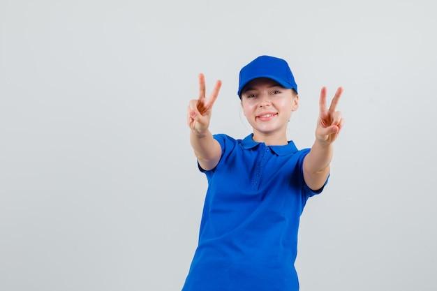 Kobieta dostawy pokazująca znak zwycięstwa w niebieskiej koszulce i czapce i wyglądająca wesoło