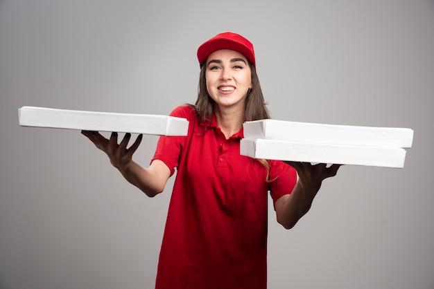 Kobieta dostawy rozdaje zamówienia na pizzę.