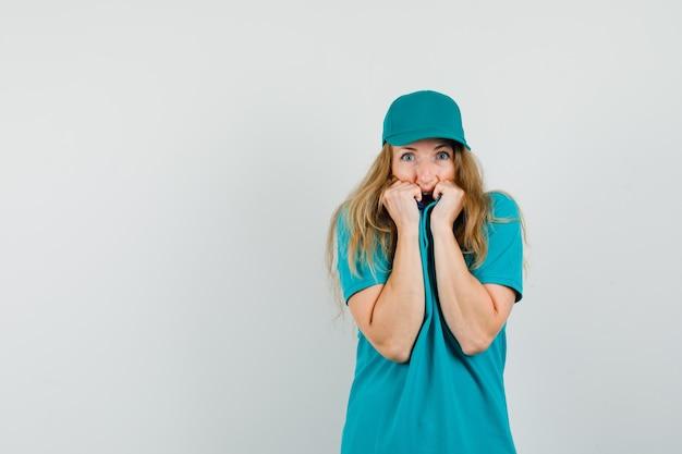 Kobieta dostawy ściągająca kołnierz na twarzy w t-shirt, czapkę i wyglądająca na przestraszoną.