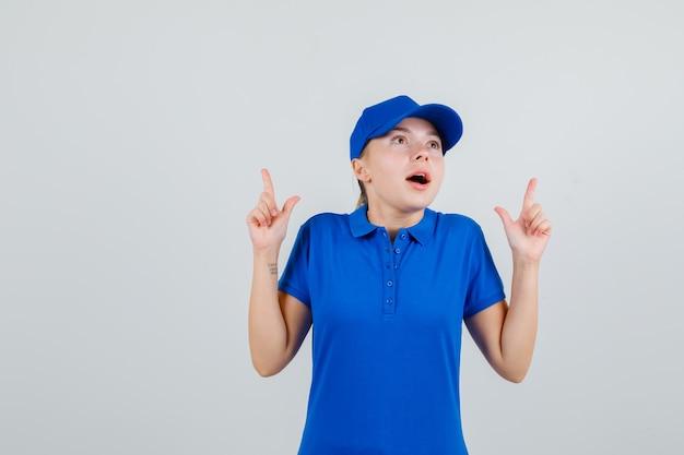 Kobieta dostawy skierowana w górę w niebieskiej koszulce i czapce i wyglądająca na zdumioną