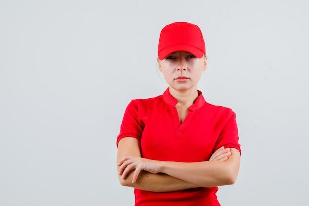 Kobieta dostawy stojącej ze skrzyżowanymi rękami w czerwonej koszulce i czapce i patrząc surowo