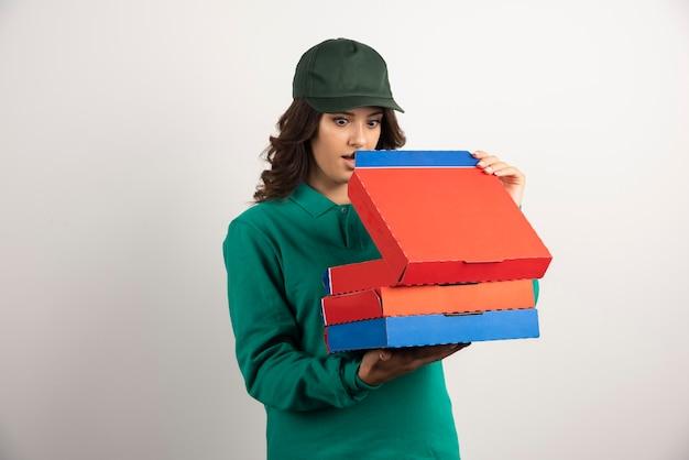 Kobieta dostawy szokująco patrząc na pizzę.