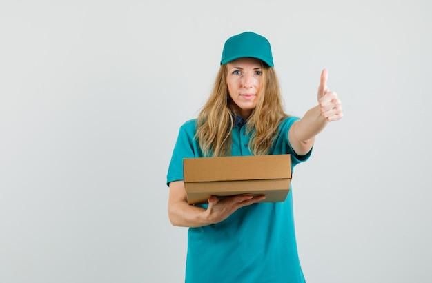 Kobieta dostawy trzyma karton i pokazuje kciuk w t-shirt, czapka