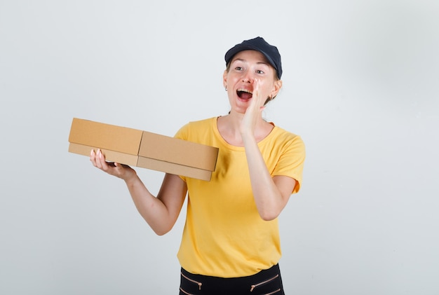 Kobieta dostawy trzymając karton i krzycząc w t-shirt, spodnie i czapkę
