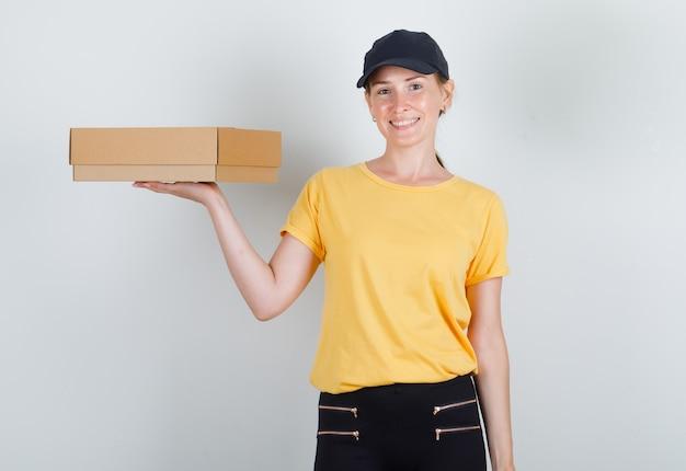Kobieta dostawy trzymając karton i uśmiechając się w t-shirt, spodnie i czapkę