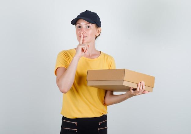 Kobieta dostawy trzymając karton z gestem ciszy w t-shirt, spodnie i czapkę