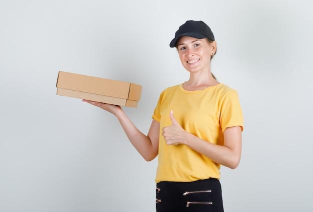 Kobieta dostawy, trzymając karton z kciukiem do góry w t-shirt, spodnie i czapkę i wyglądający na zadowolonego