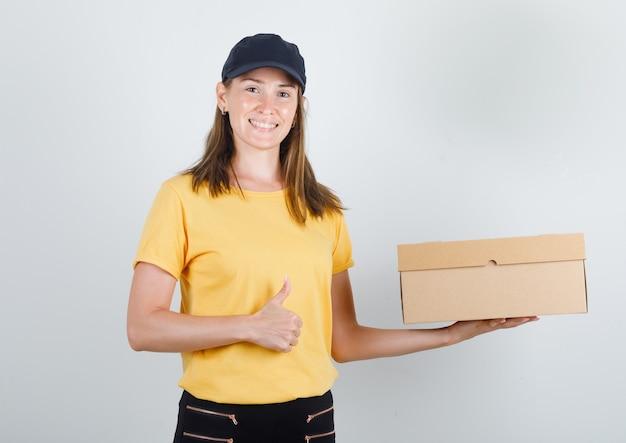 Kobieta dostawy trzymając karton z kciukiem w t-shirt, spodnie i czapkę i patrząc wesoło
