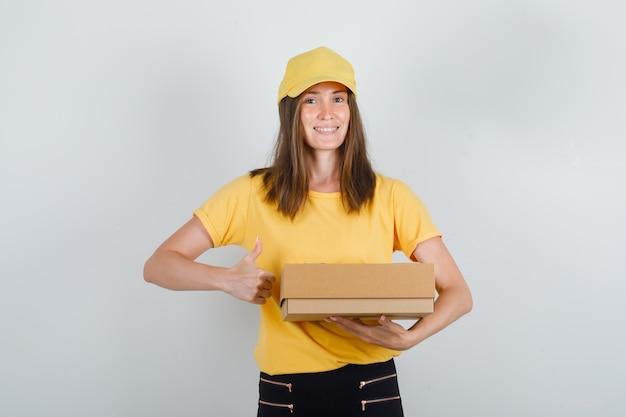 Kobieta dostawy trzymając karton z kciukiem w t-shirt, spodnie i czapkę i wyglądający wesoło
