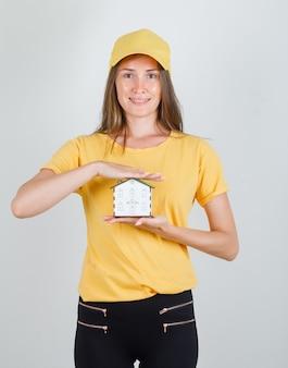 Kobieta dostawy trzymając model domu w t-shirt, spodnie, czapkę i wesoły wygląd.