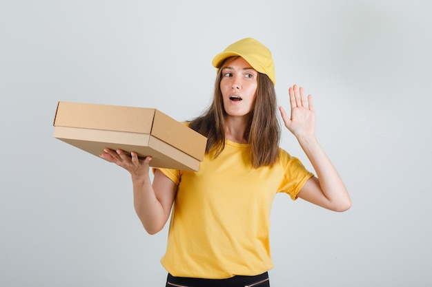 Kobieta dostawy trzymając pudełko z ręką przy uchu w koszulce, czapce, spodniach i szuka zainteresowania