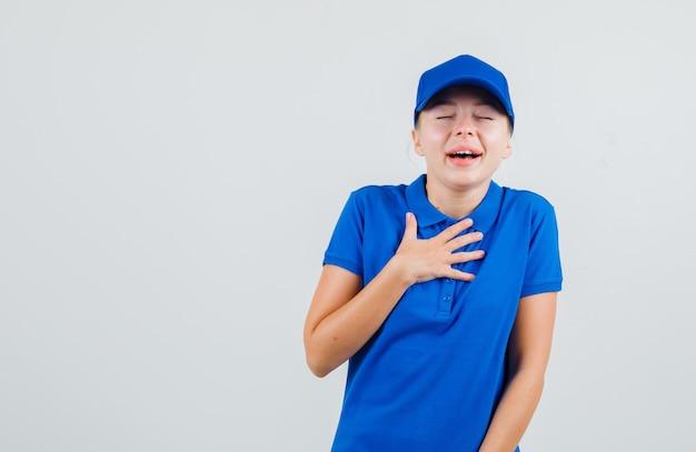 Kobieta dostawy, trzymając rękę na klatce piersiowej w niebieskiej koszulce i czapce i patrząc szczęśliwy