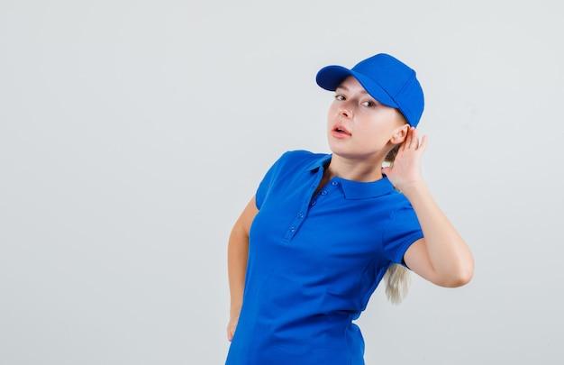 Kobieta dostawy trzymając rękę za ucho w niebieskiej koszulce i czapce i patrząc zaciekawiony