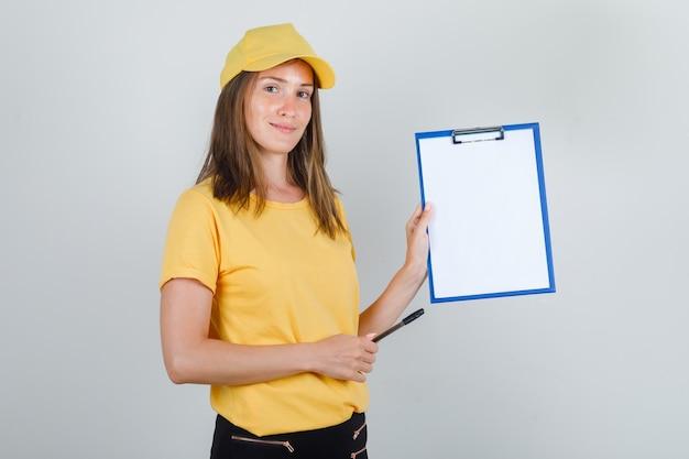 Kobieta dostawy, trzymając schowek i długopis w t-shirt, spodnie, czapkę i wyglądający wesoło