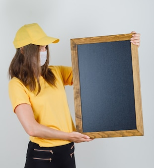 Kobieta dostawy trzymając tablicę w t-shirt, spodnie, czapkę i maskę