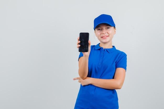Kobieta dostawy trzymając telefon komórkowy w niebieskiej koszulce i czapce i patrząc wesoło