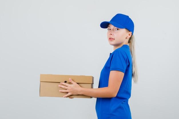 Kobieta dostawy trzymająca karton w niebieskiej koszulce i czapce i wyglądająca pewnie.
