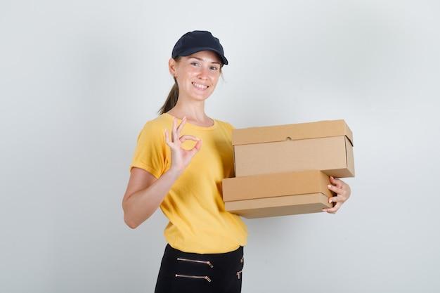 Kobieta dostawy trzymająca kartony z napisem ok w koszulce, spodniach, czapce i wyglądająca wesoło.