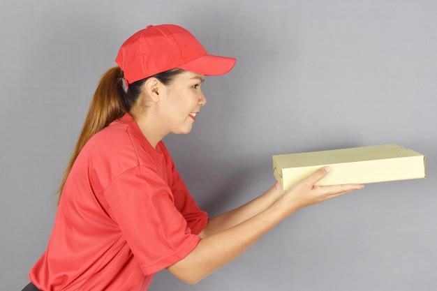 Kobieta dostawy trzymająca pudełko po pizzy na szaro