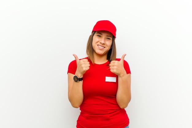 Kobieta dostawy uśmiecha się radośnie i wygląda na szczęśliwą, czuje się beztrosko i pozytywnie z obydwoma kciukami w górę przeciwko bielowi