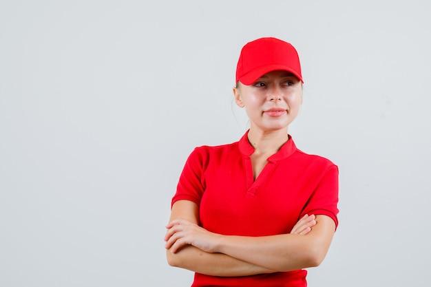 Kobieta dostawy w czerwonej koszulce i czapce odwracając wzrok ze skrzyżowanymi rękami i patrząc z nadzieją