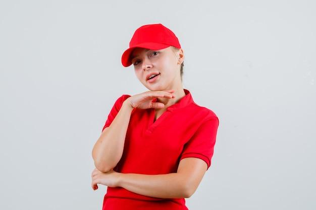 Kobieta dostawy w czerwonej koszulce i czapce podpierająca podbródek na podniesionej ręce i wyglądająca uroczo